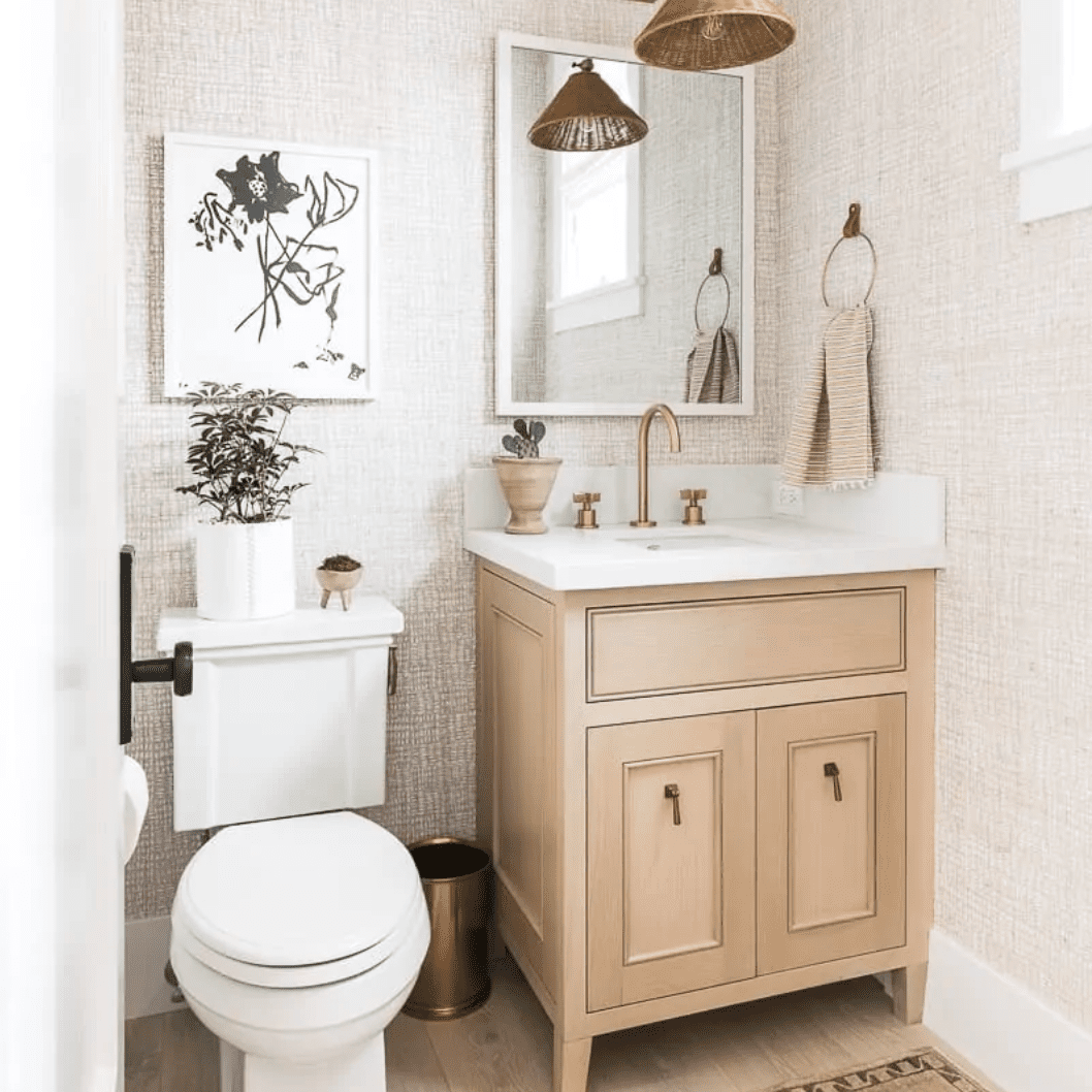 A powder room with textured pink walls and a light brown printed rug