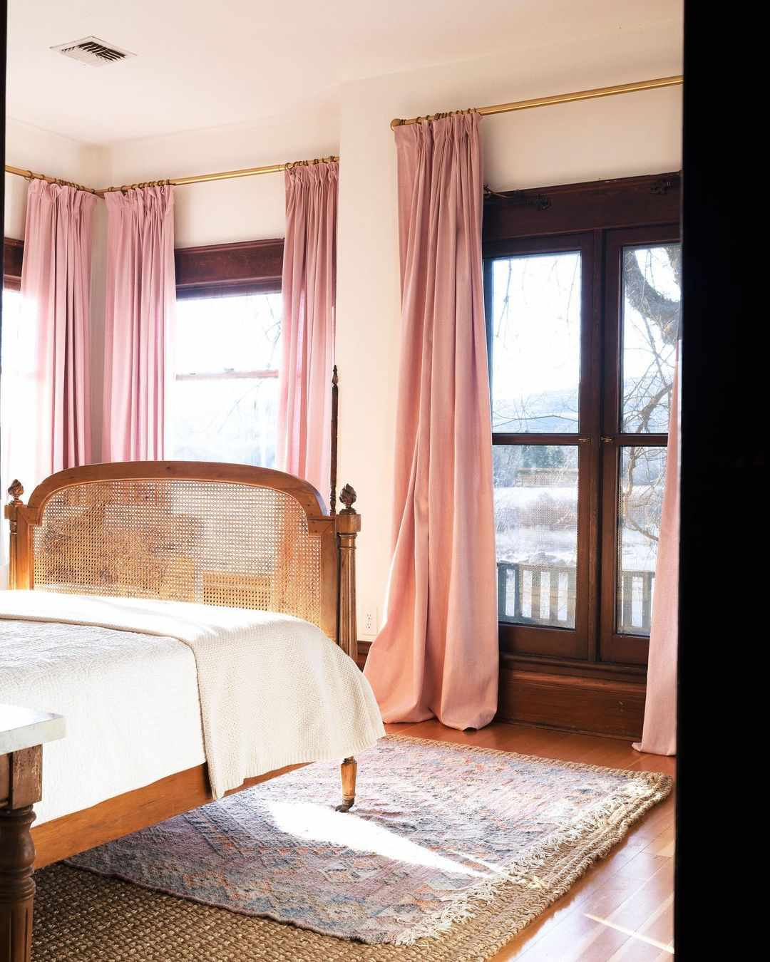 Pink drapes hang near the ceiling in a bedroom.