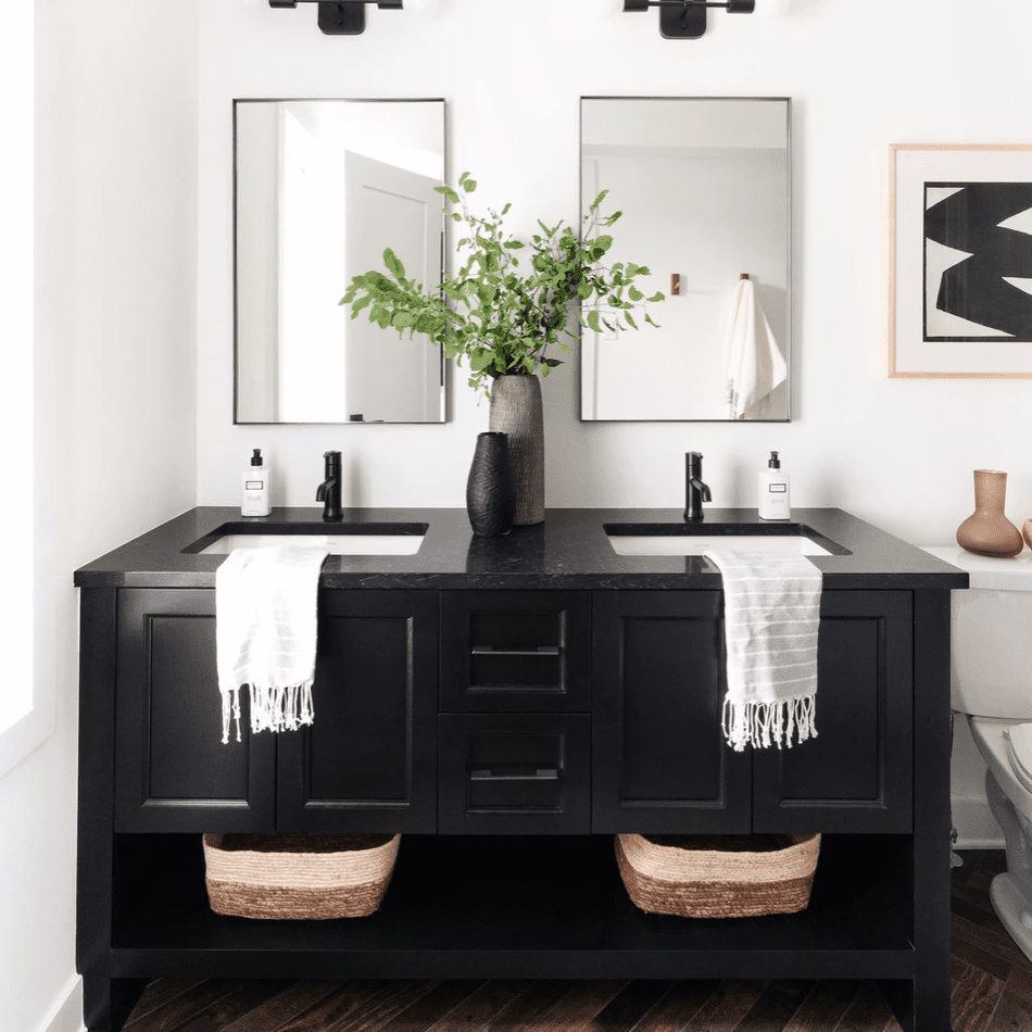 A black double vanity outfitted with plants, baskets, and plush towels