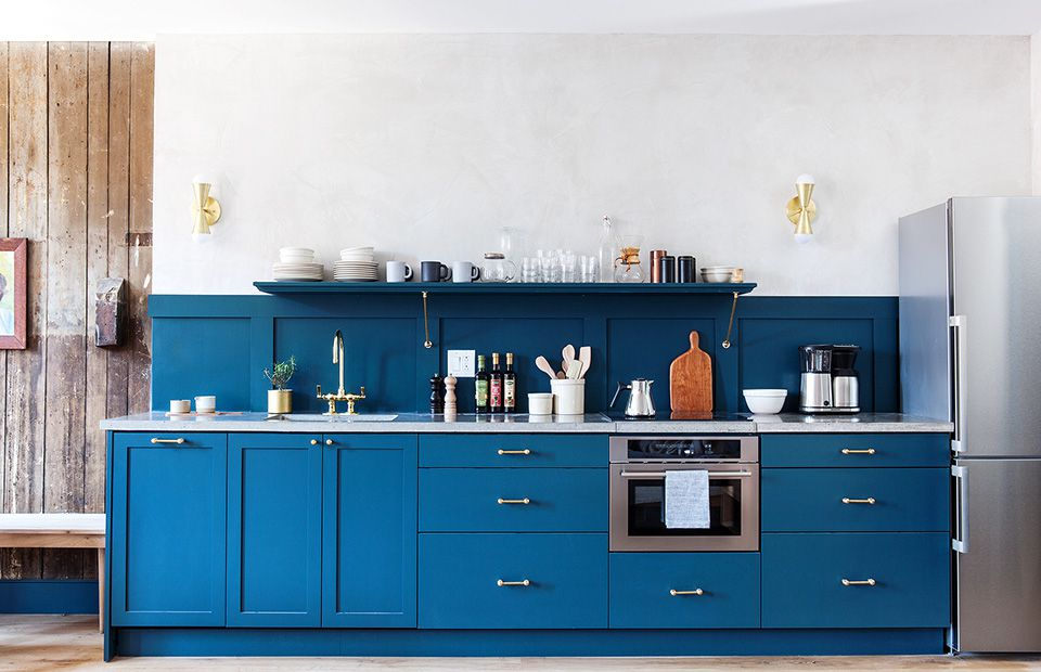 A kitchen with bold blue cabinets
