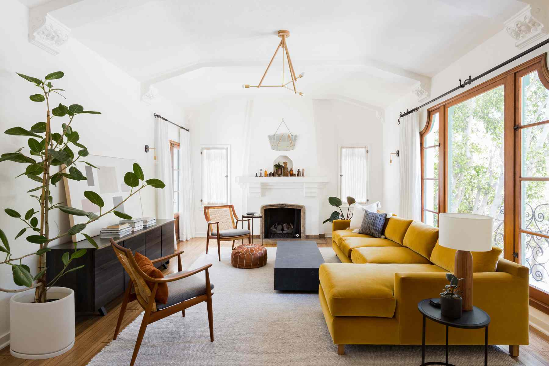 Eclectic living room with mustard velvet sofa and wood accent chairs