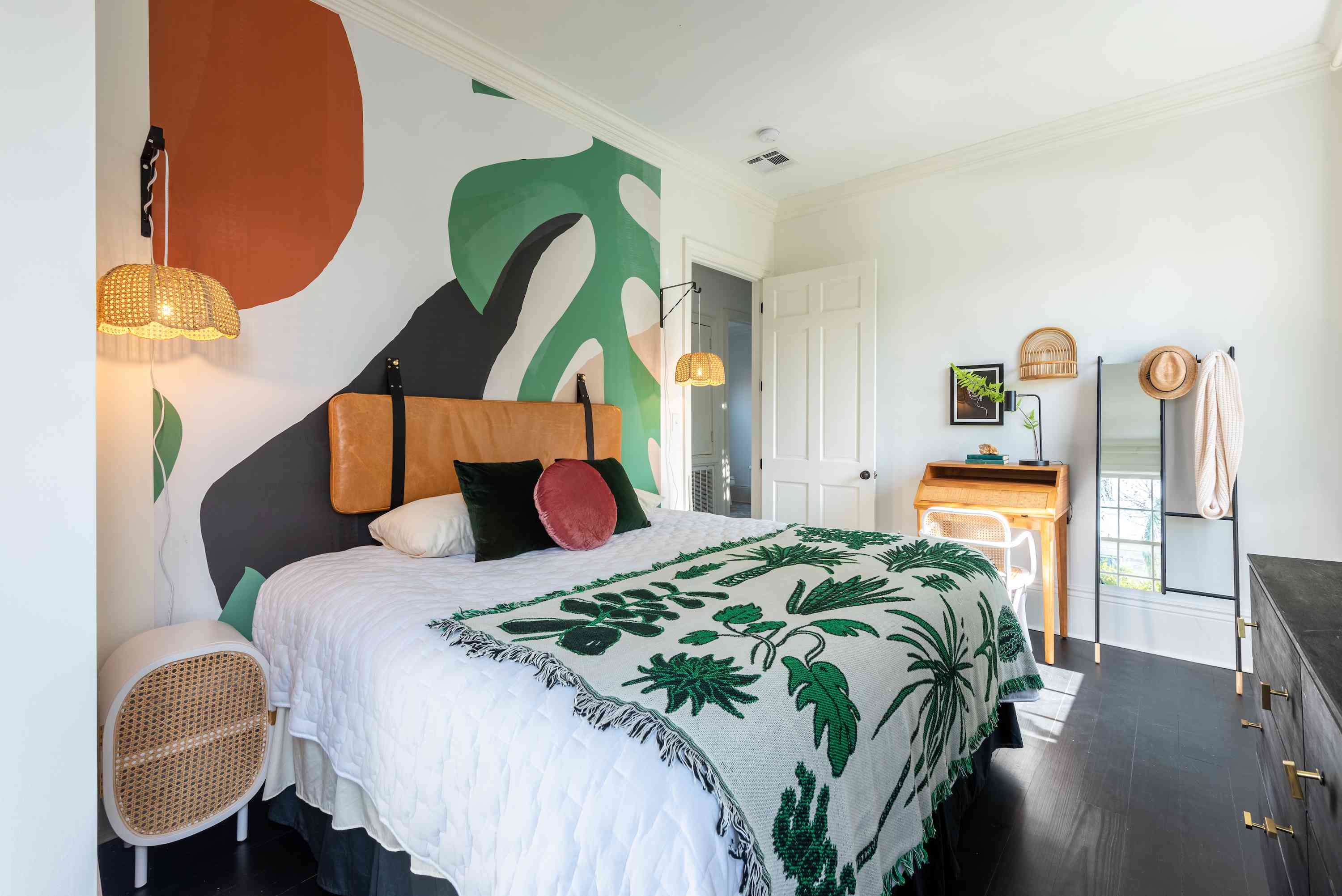 Bedroom with tropical inspired blanket and bold graphic mural.