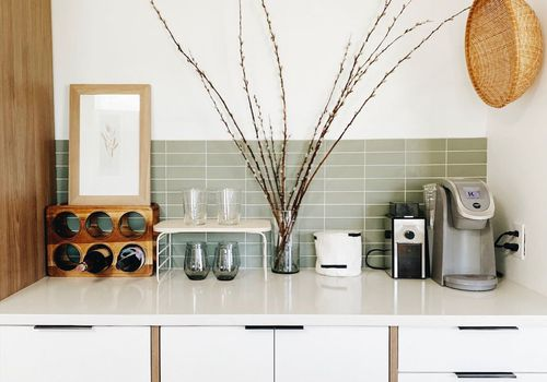 Coffee maker and coffee bar on white kitchen counter.