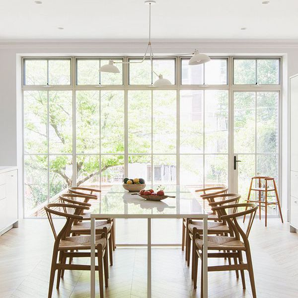 an all-white kitchen with a dining table