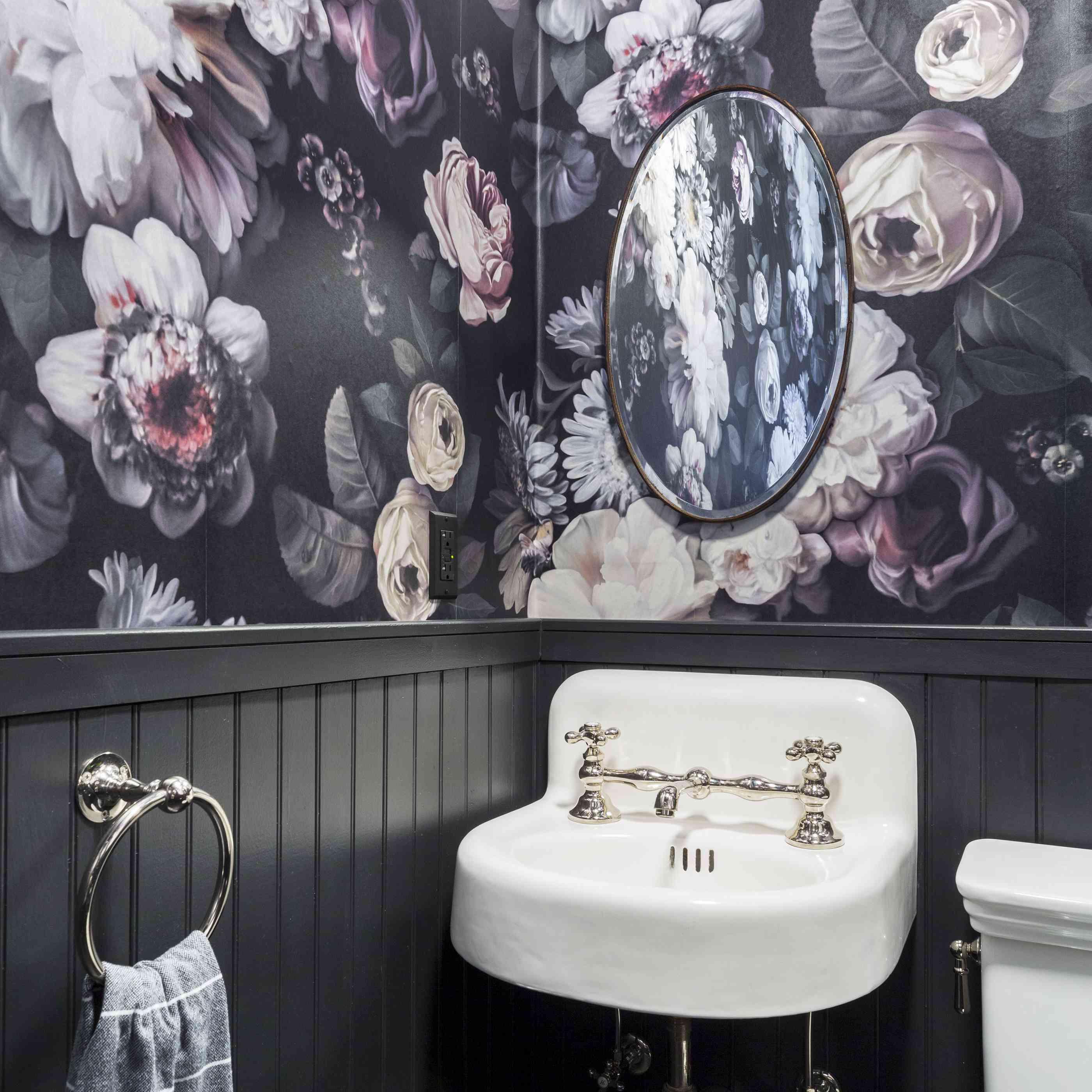 Black bathroom with floral wallpaper.