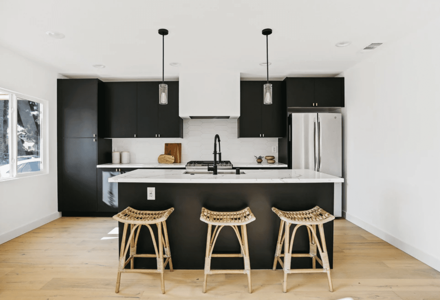 A kitchen with black cabinets and a white backsplash, crafted from hexagonal tiles