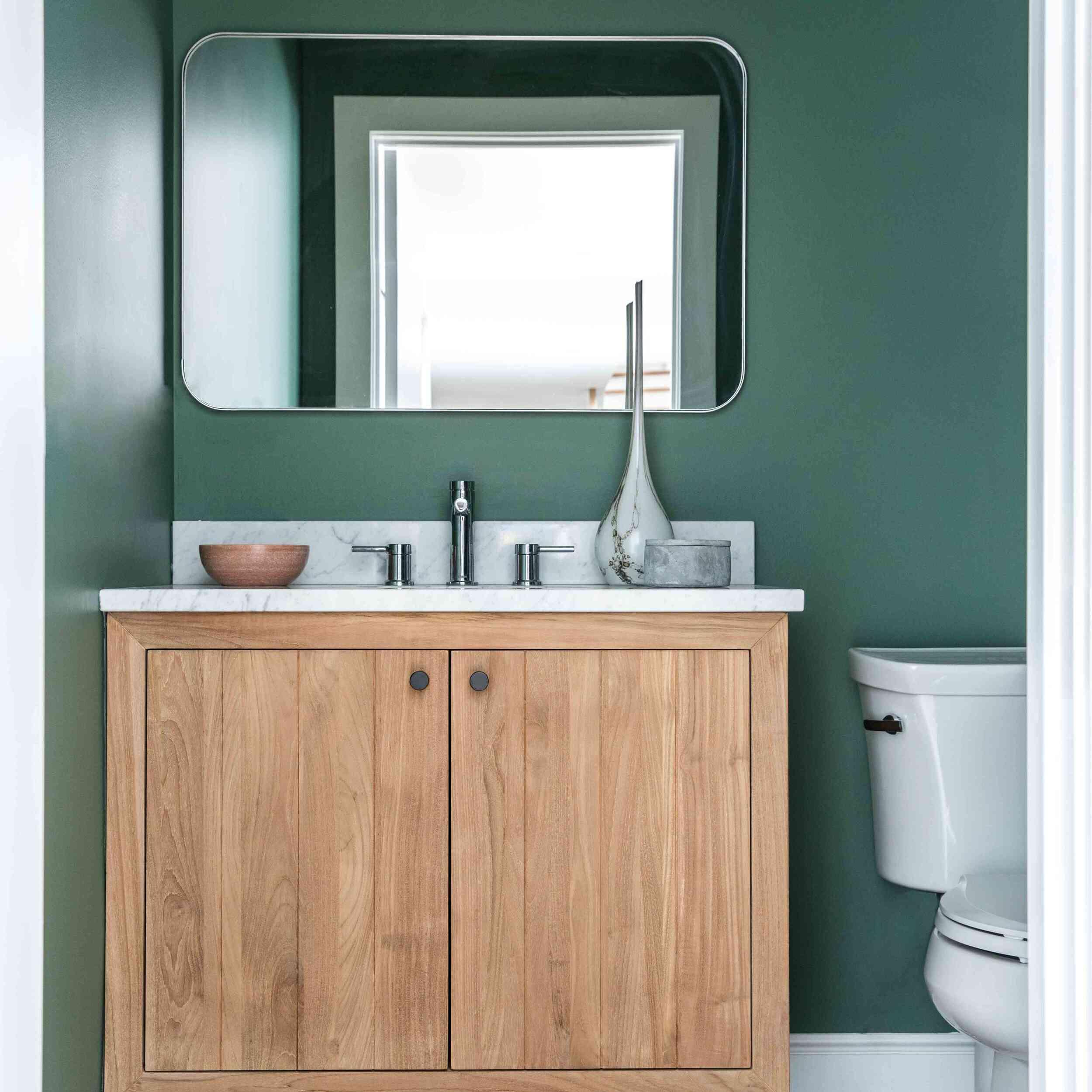 A half-bathroom with dark green walls