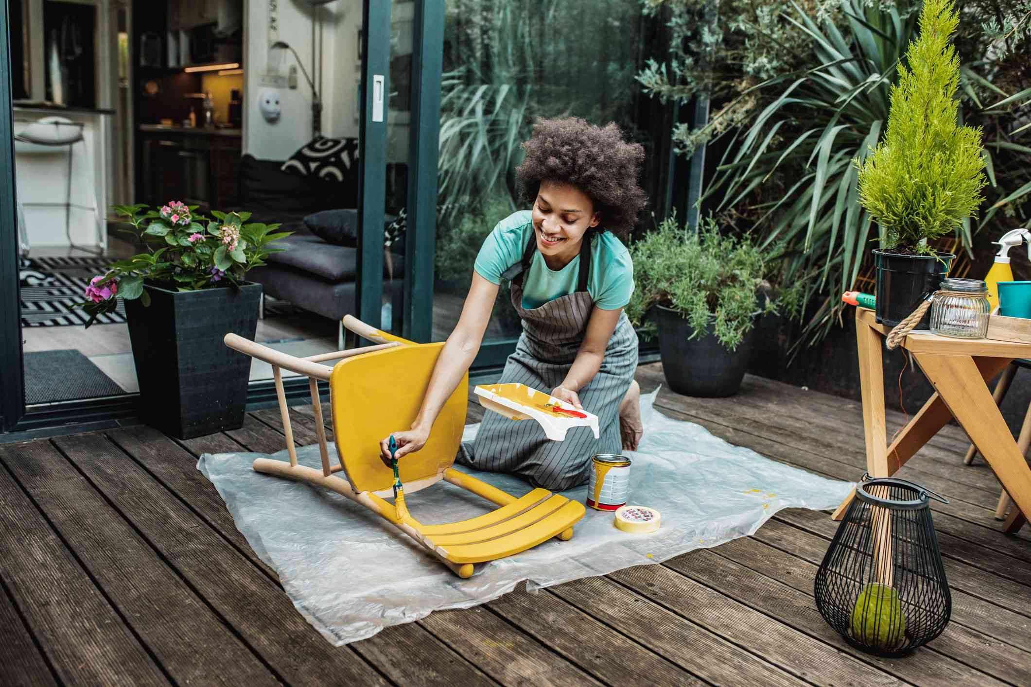 Woman paints chair yellow