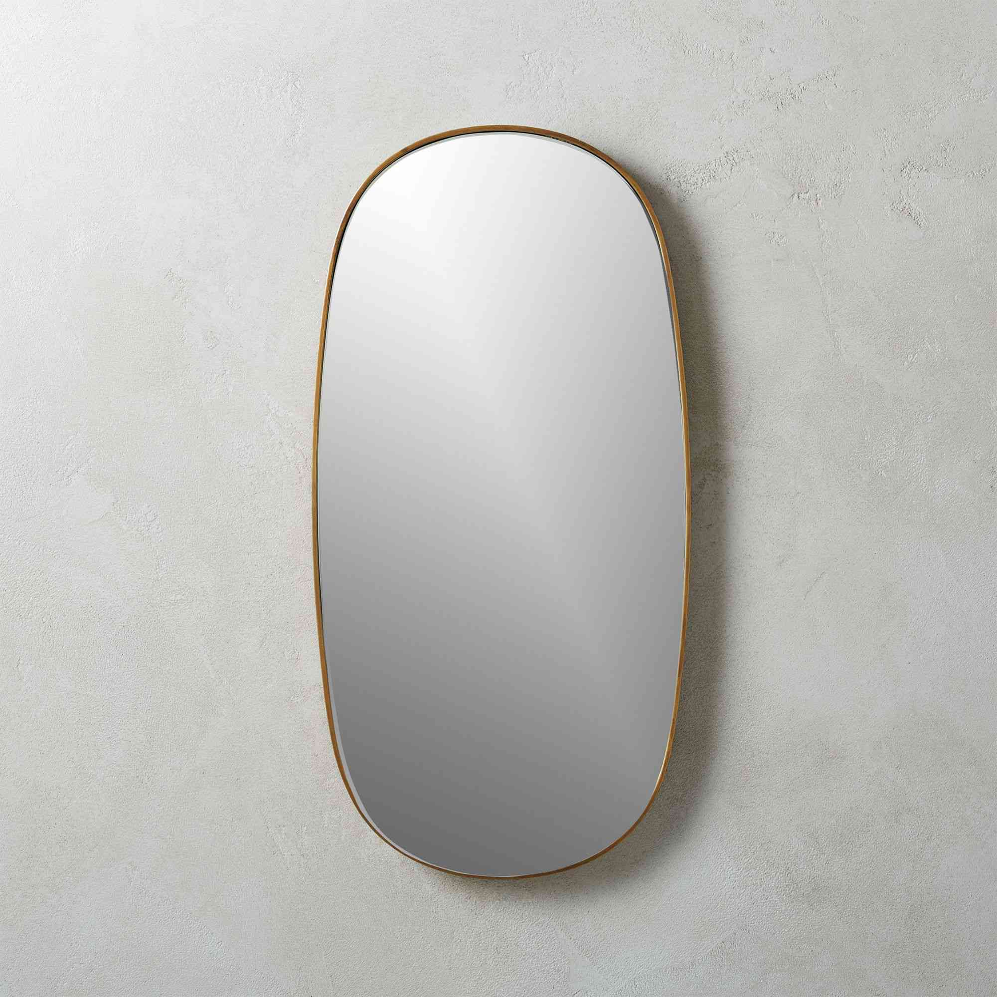 A CB2 oval mirror with an iron frame finished in antique-brass.