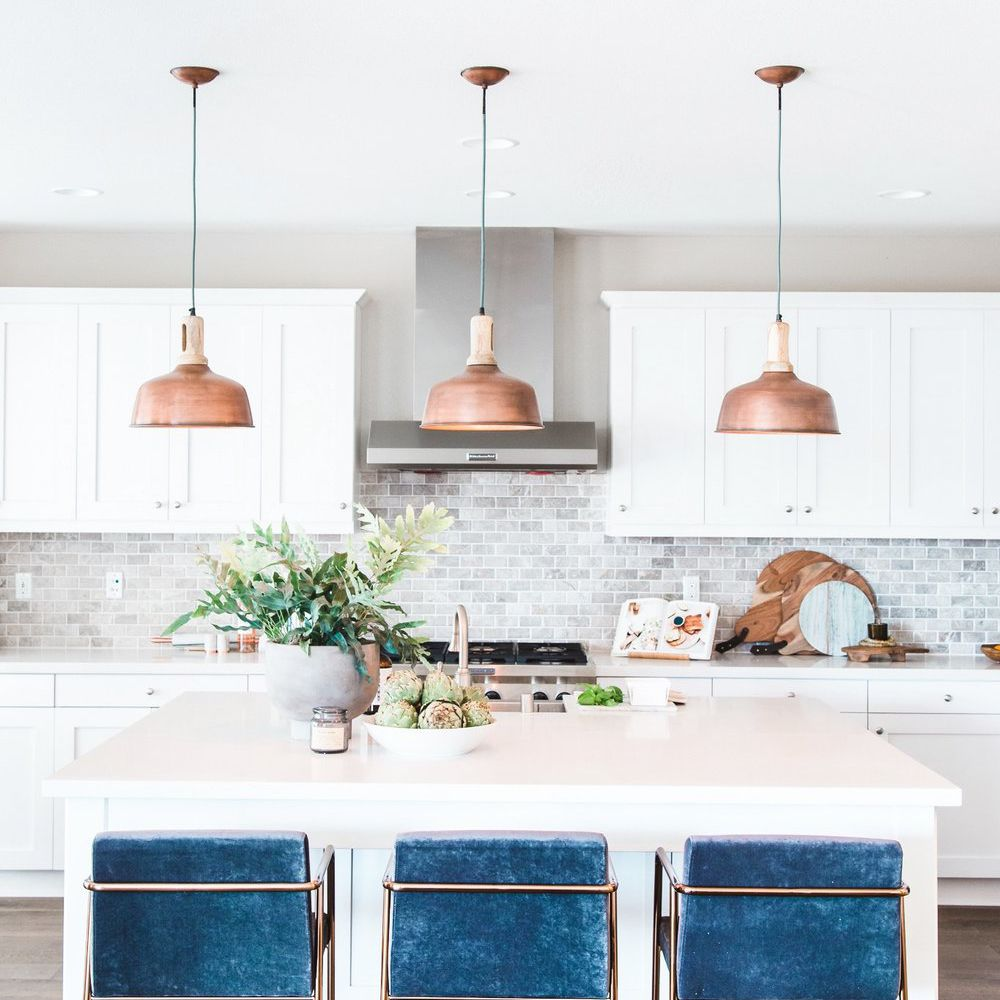 White kitchen with copper pendants and blue velvet counter stools