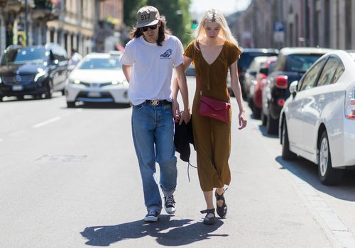 couple walking with heads down looking somber