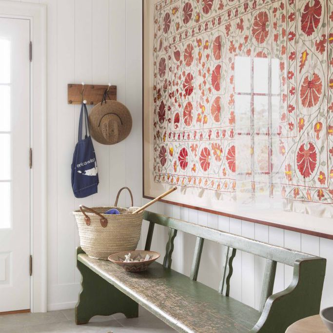 An entryway with a distressed green bench and a large piece of art