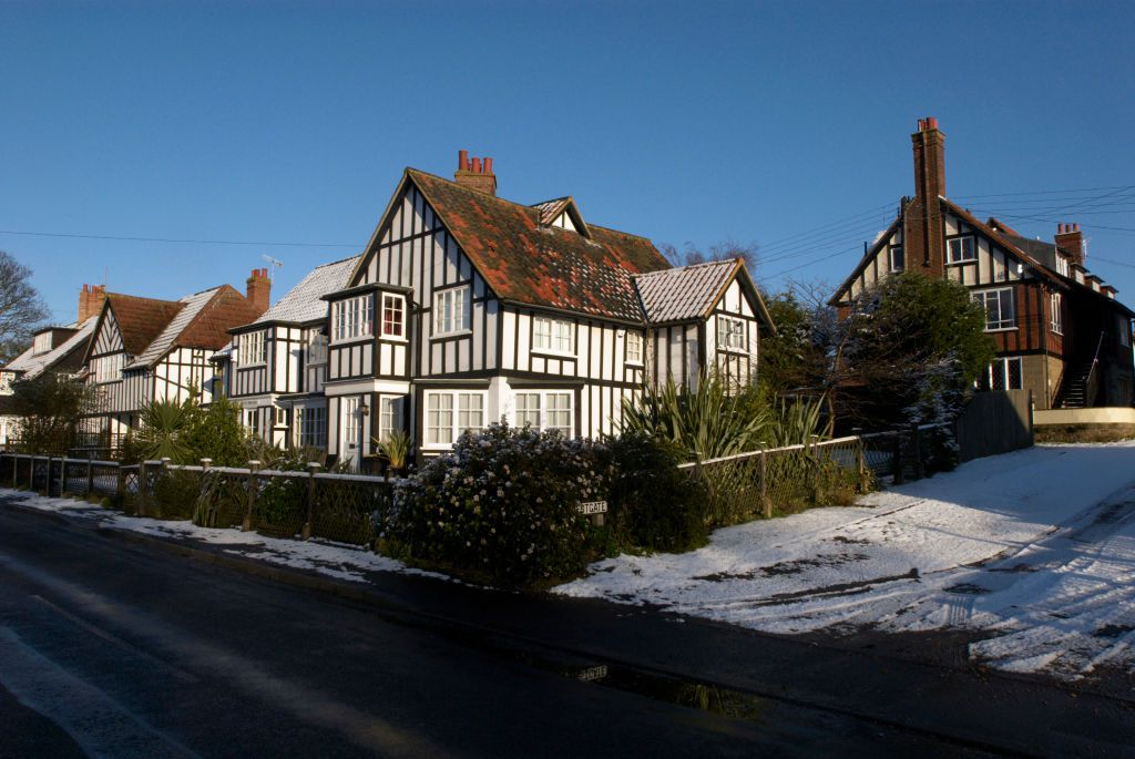 what is a tudor home? a white tudor home on the corner of a snowy street in the UK