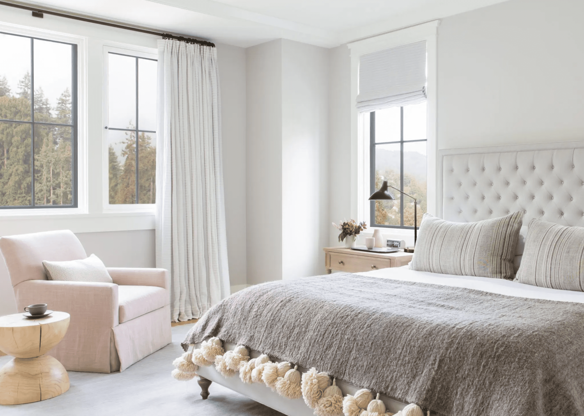 A white bed with a lavender throw blanket on it