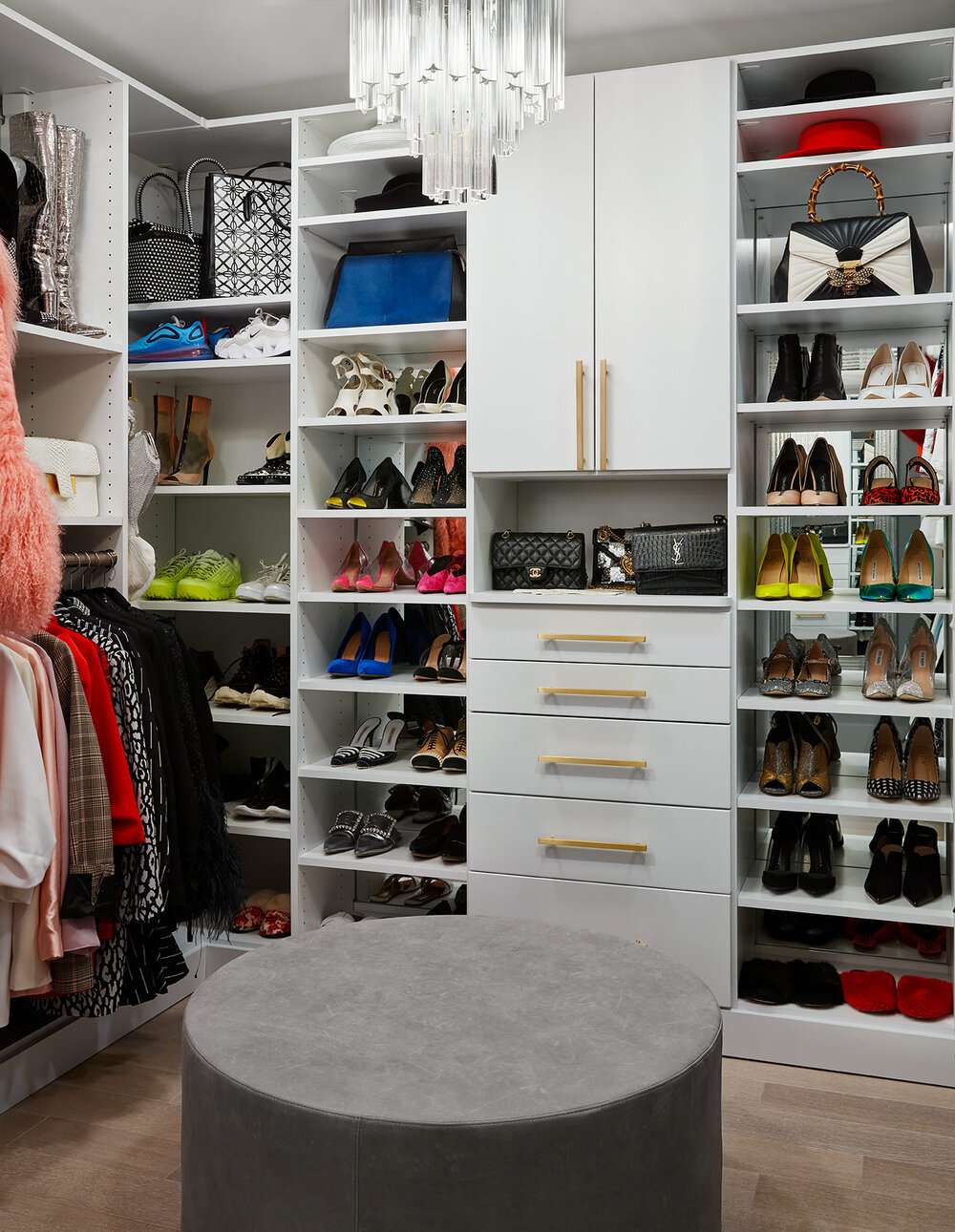 Closet with mirrors, gold hardware, and chandelier