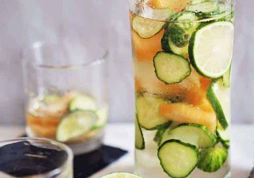 White sangria in a pitcher filled with cucumber, lime and melons.