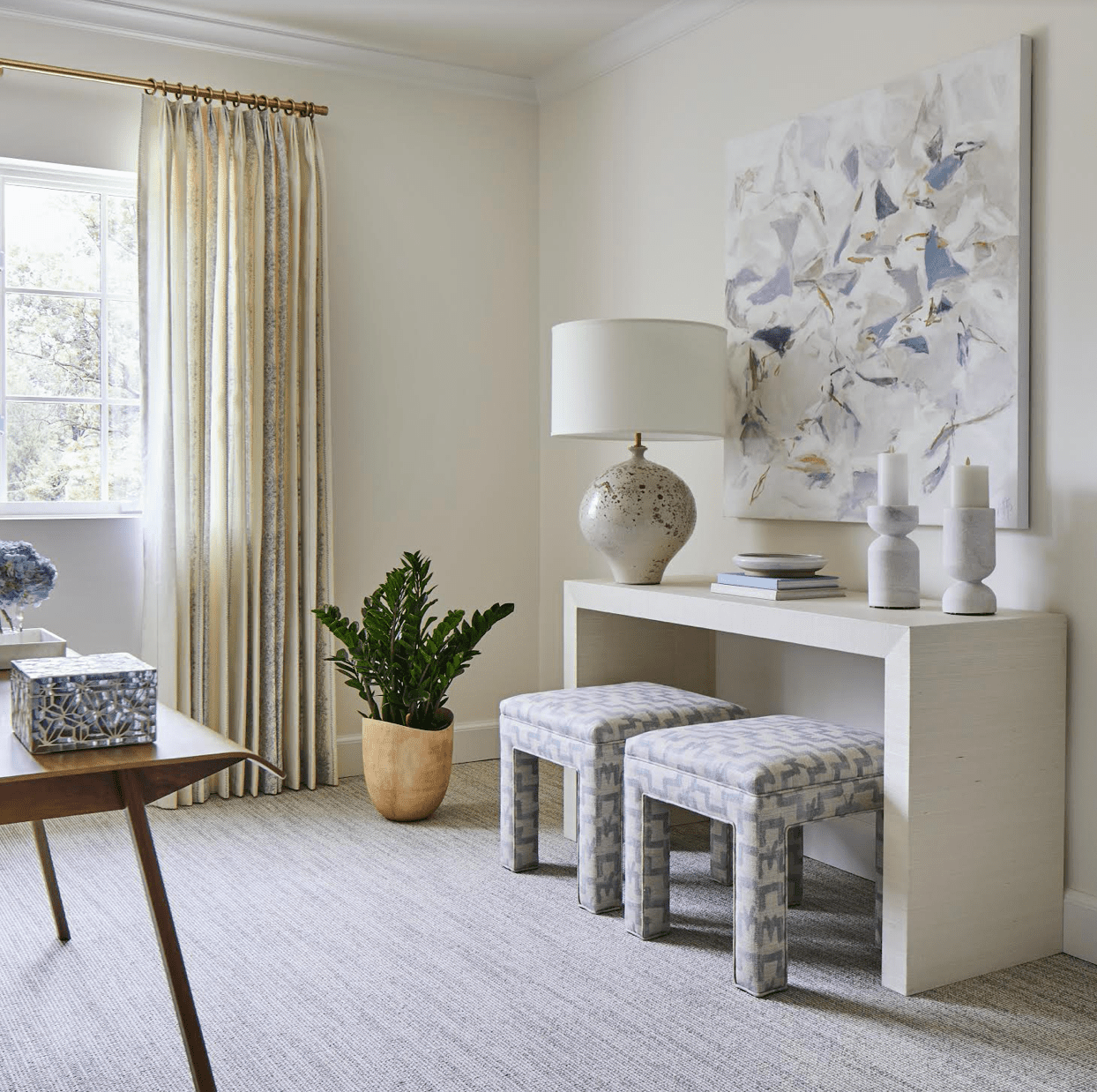 Clean and tidy living room with neutral art and stools.