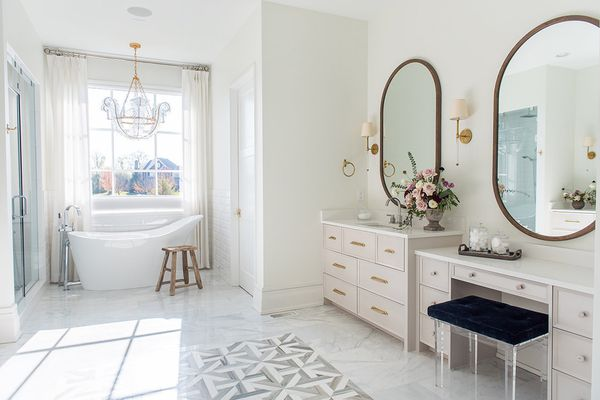 Master bathroom with oval vanity mirrors, chandelier above soaking tub