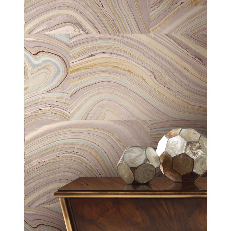Tiled pink marbled wallpaper behind a console table with two round sculptures.