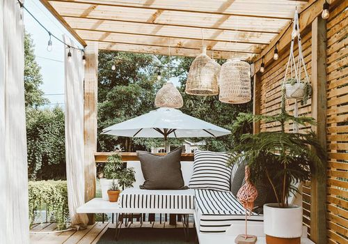 Outdoor wooden pergola with floating sofa underneath.