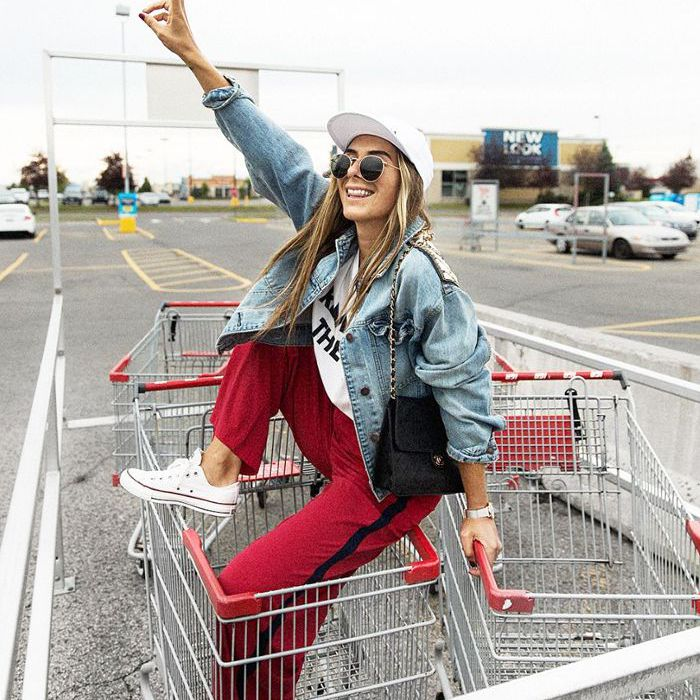 Young person sits in shopping cart holding up peace sign