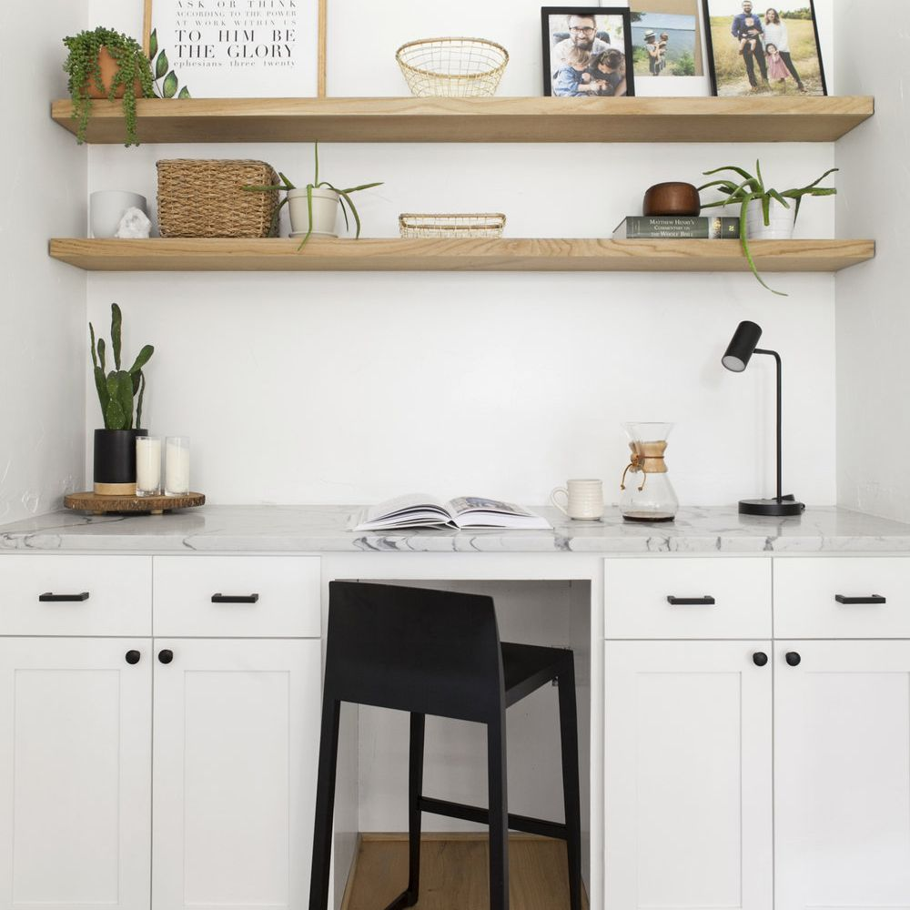 home office with floating shelves and a black desk chair