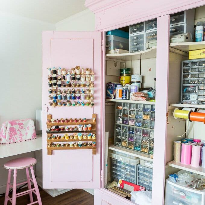 A pastel pink wardrobe filled with organized craft supplies