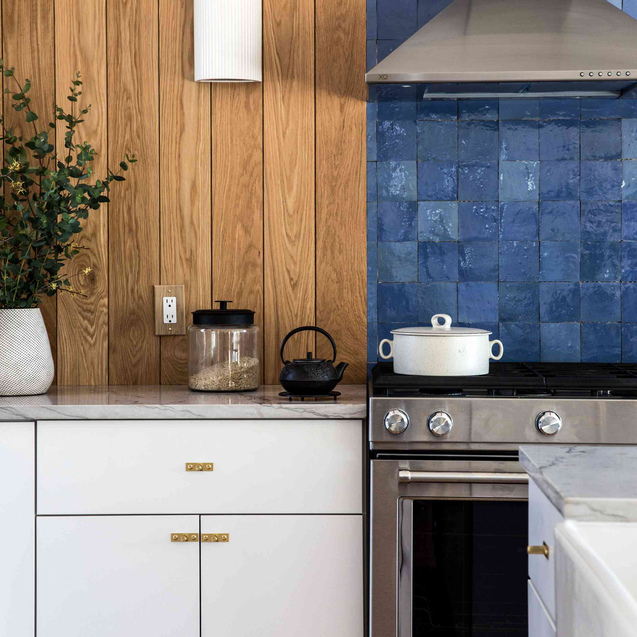 A wood-lined kitchen with white cabinets and a bold blue backsplash