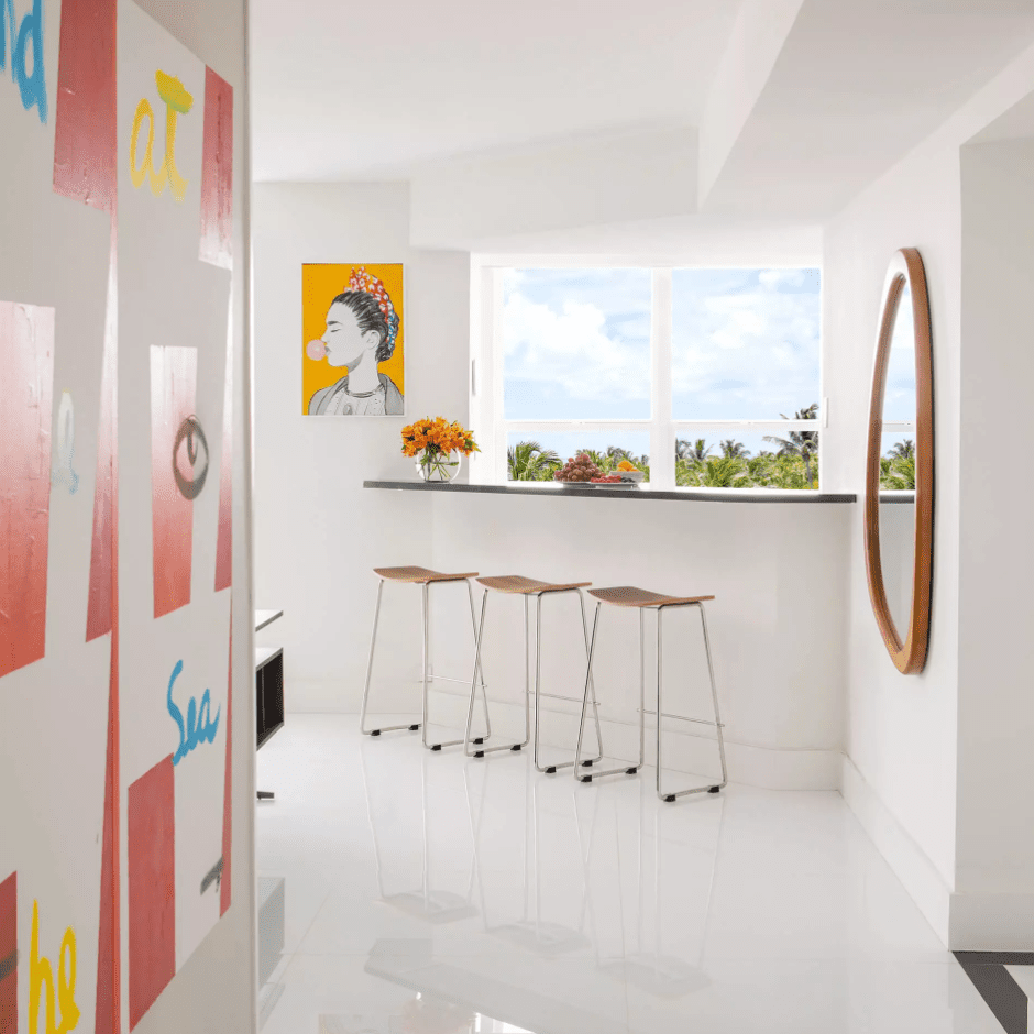 A hallway leading into a kitchen with a diagonal bar