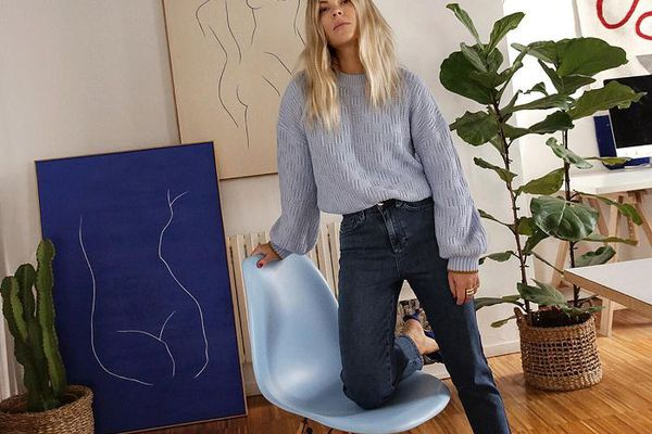 Woman kneeling on a chair in a living room with plants and art