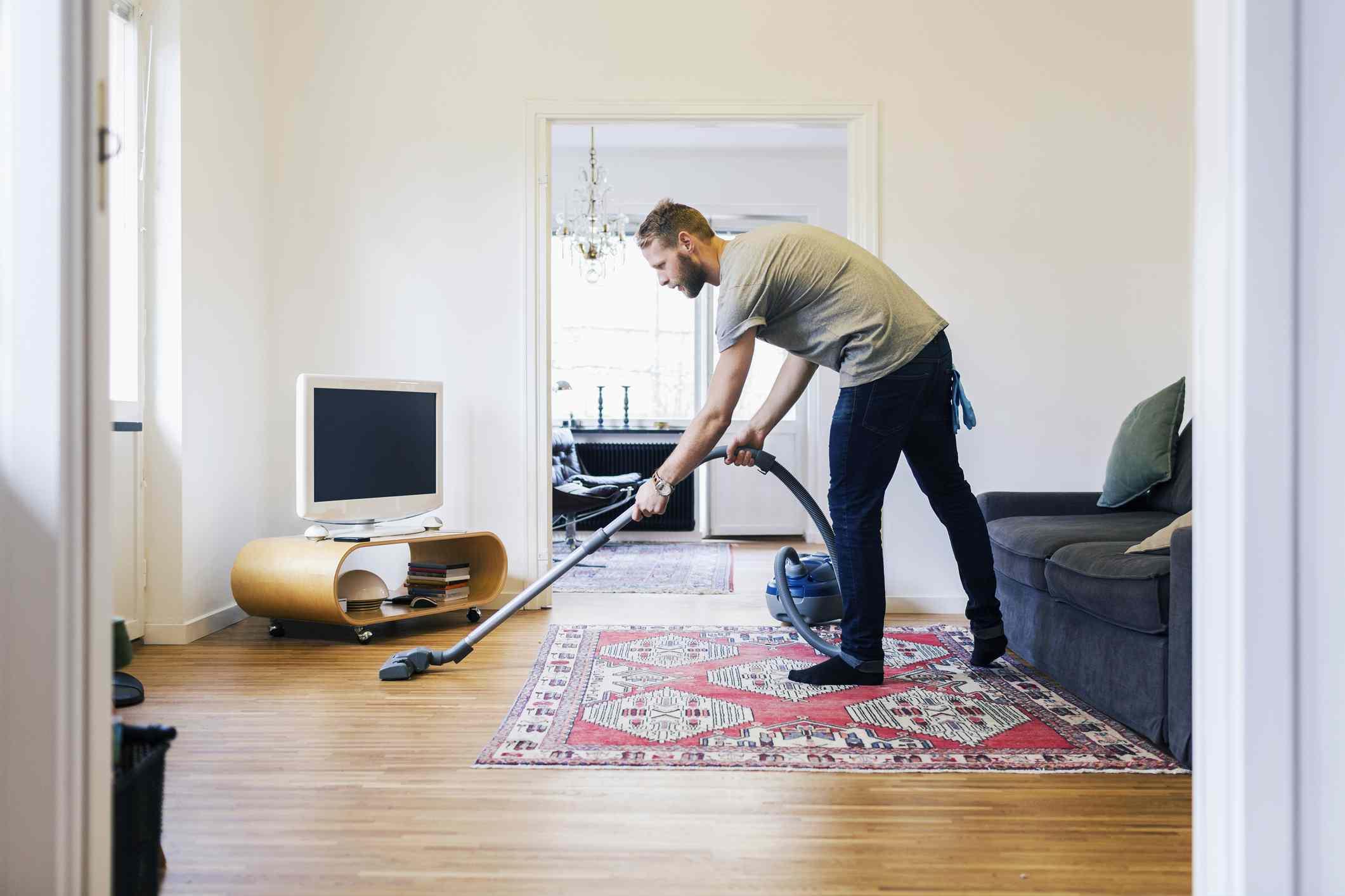 Man vacuums floor in living room