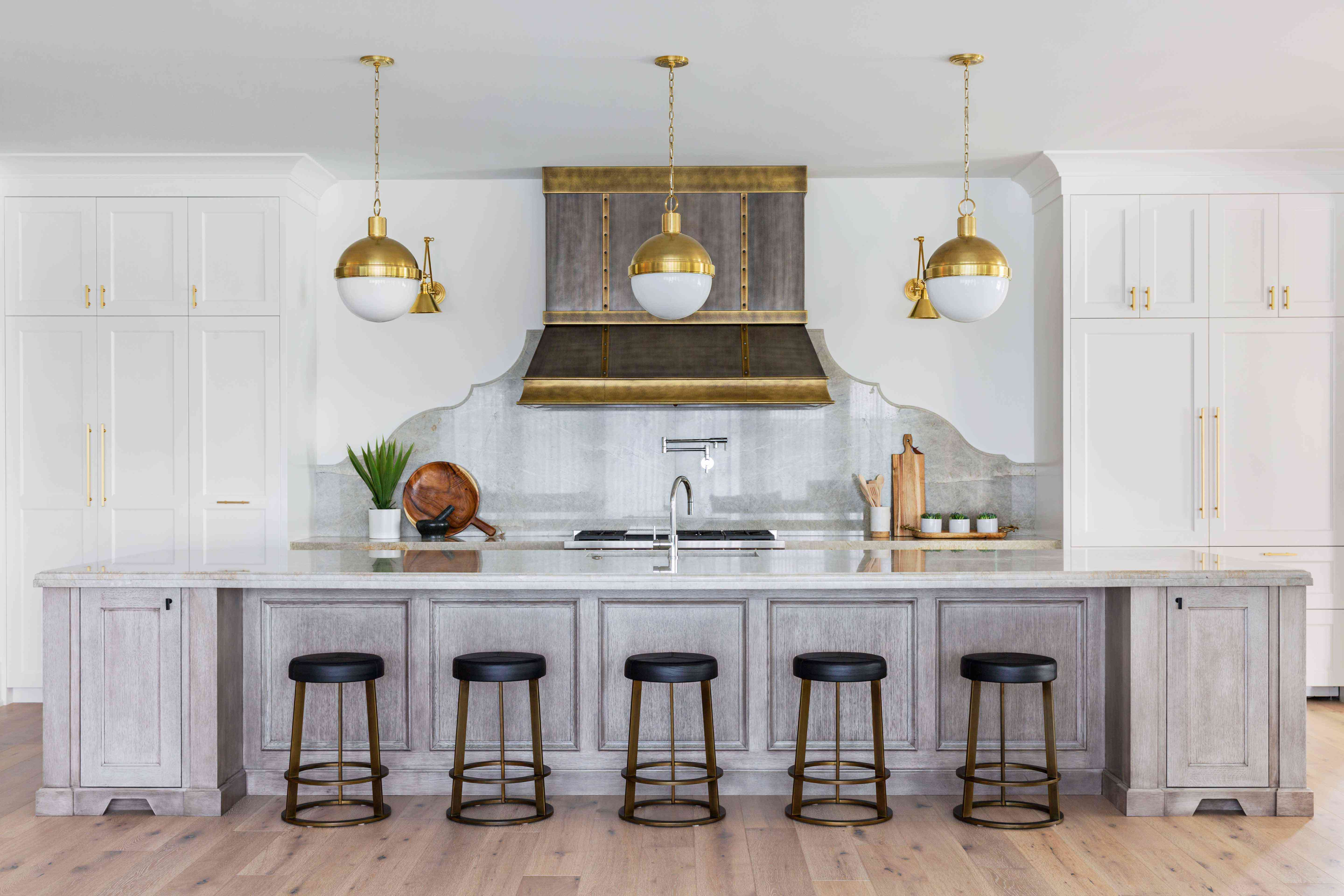 Kitchen with large wood island and brass patinaed oven hood