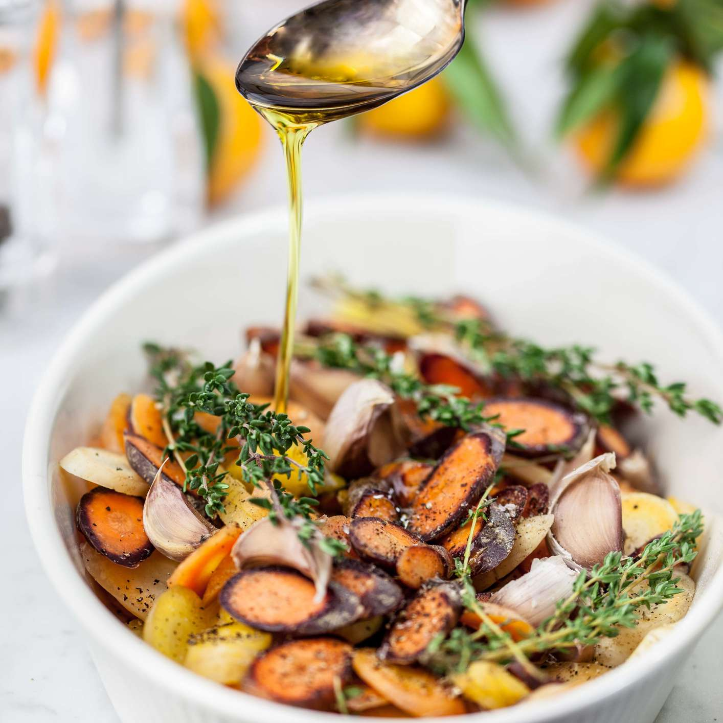 A drizzle of olive oil on a bowl of roasted vegetables