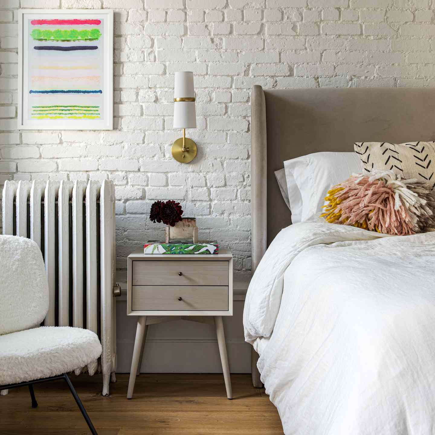 White bed against a white brick wall.