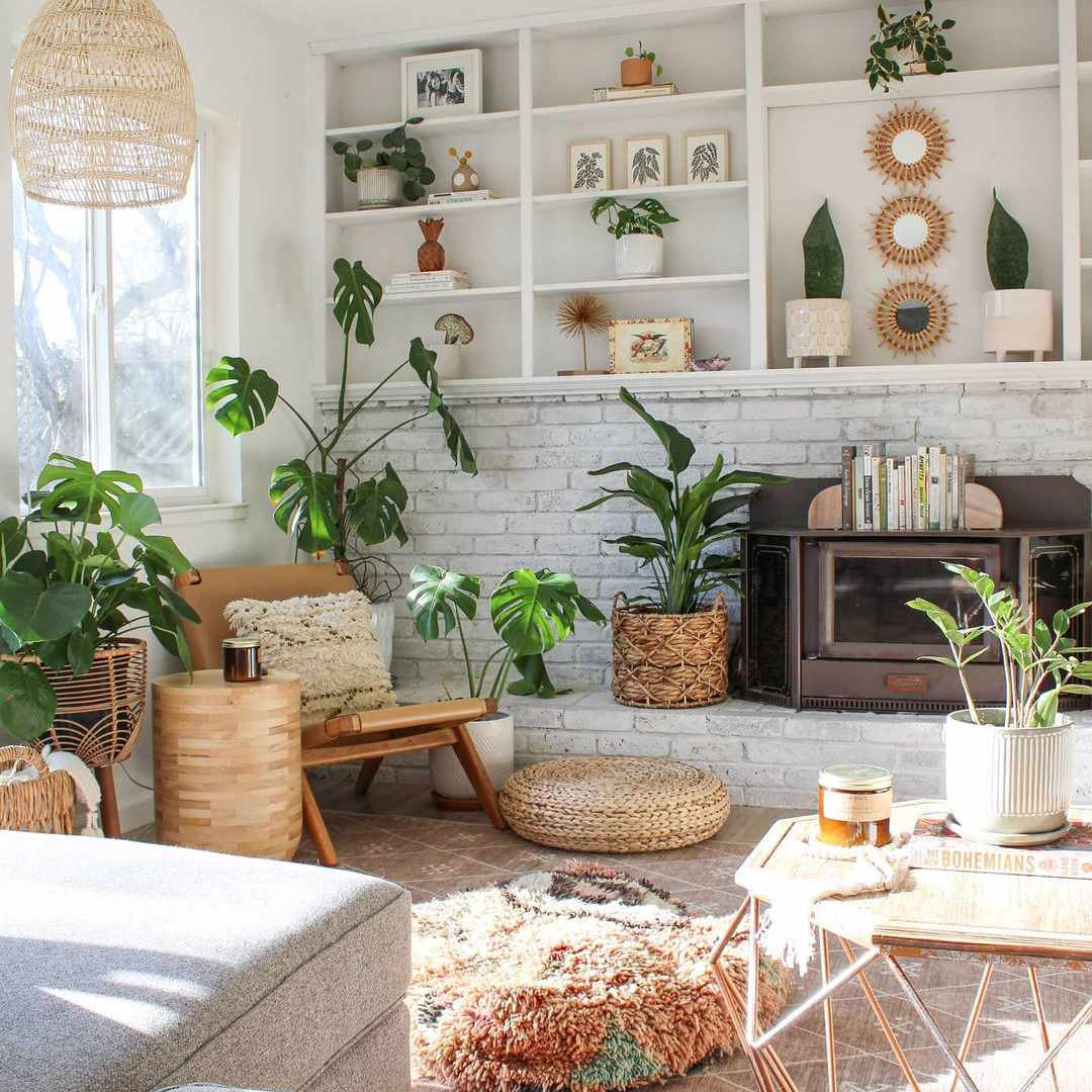 Living room filled with plants and rattan accents.