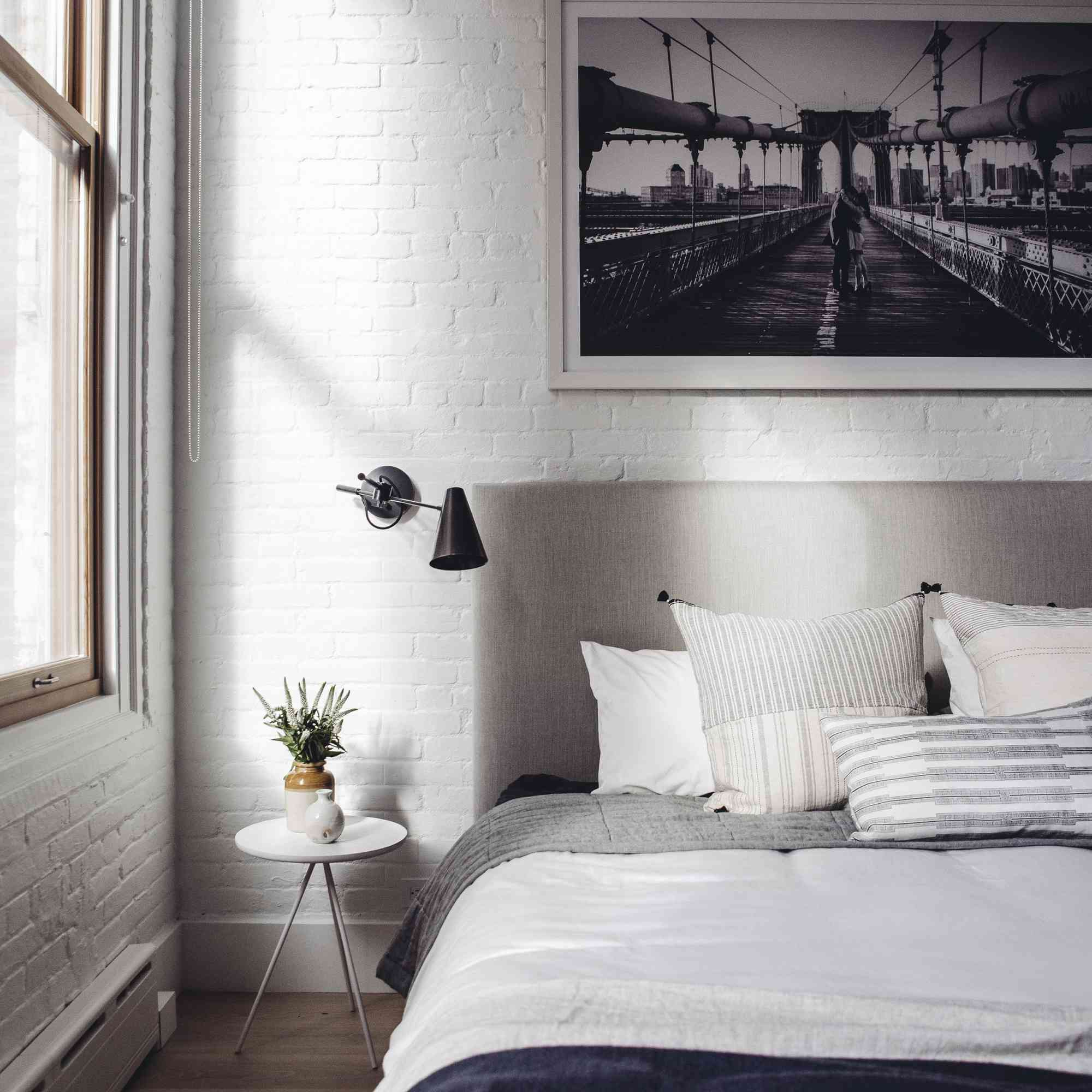 White brick bedroom with light linens and industrial elements