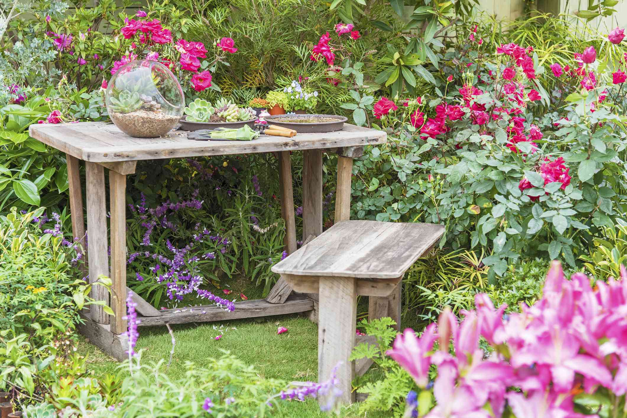 A wooden bench next to a potting table.