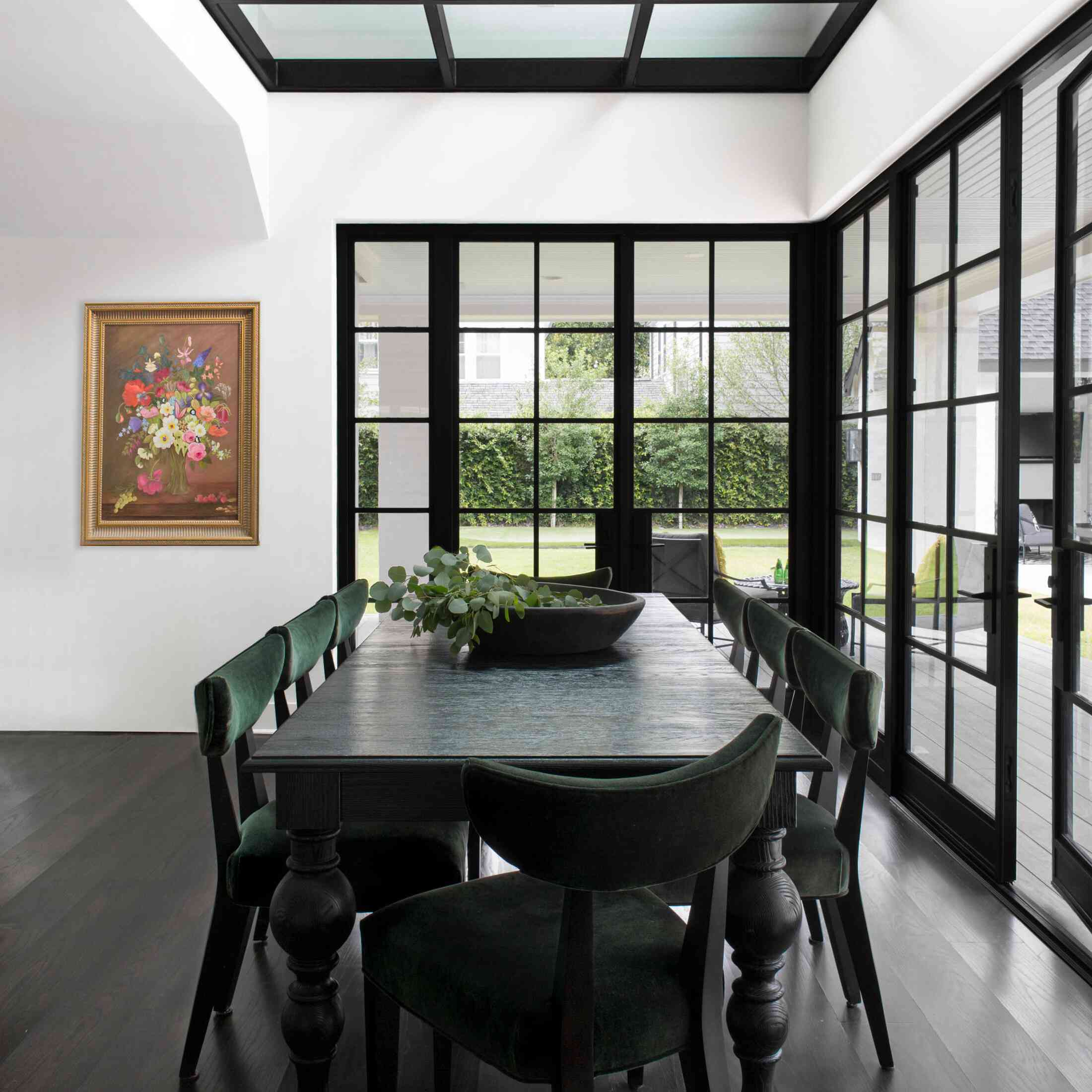 A black dining room table with dark green chairs and a matching centerpiece