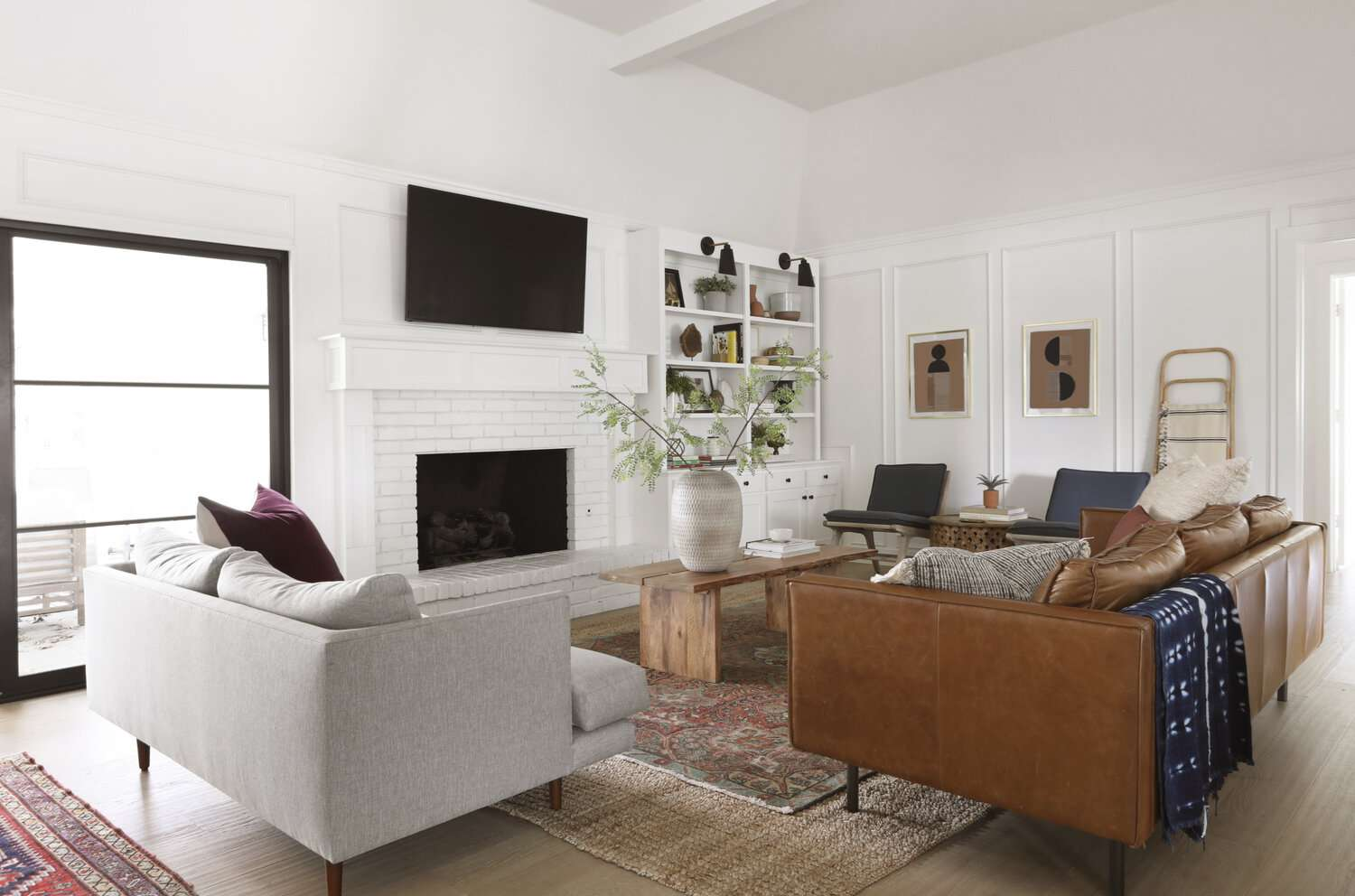 Crisp living room with white fireplace.