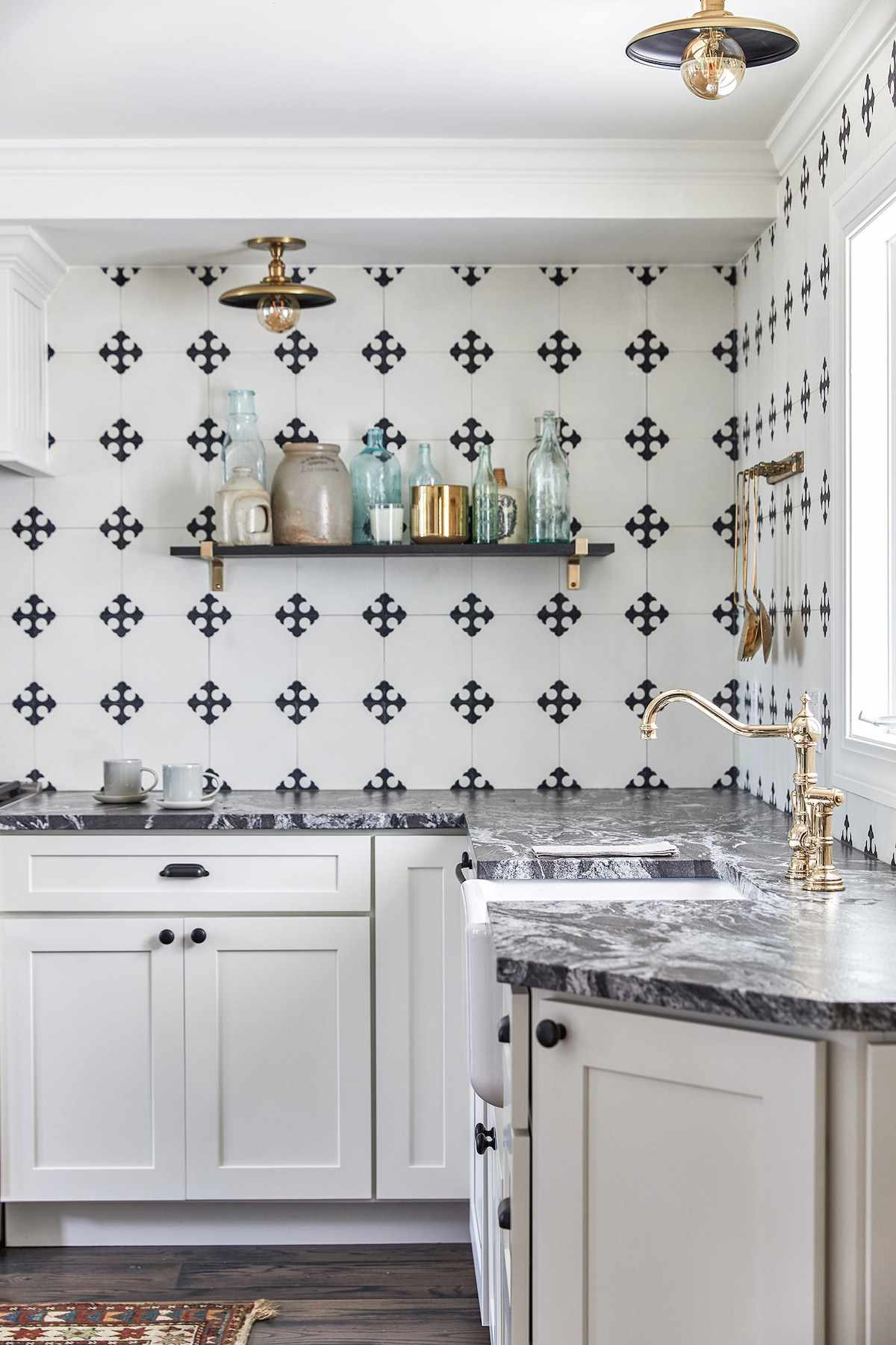 A kitchen with striated marble countertops and a bold backsplash crafted from black and white tiles