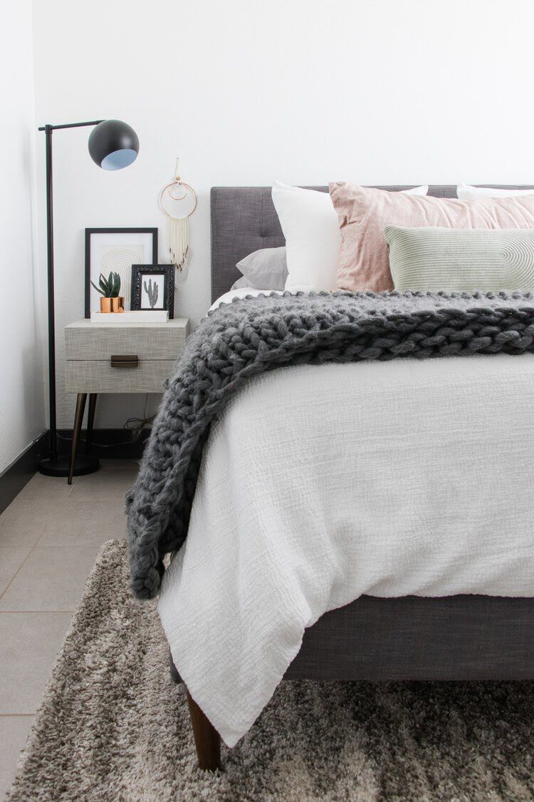 a bedroom with a gray headboard, white pillows, and a large lavender pillow
