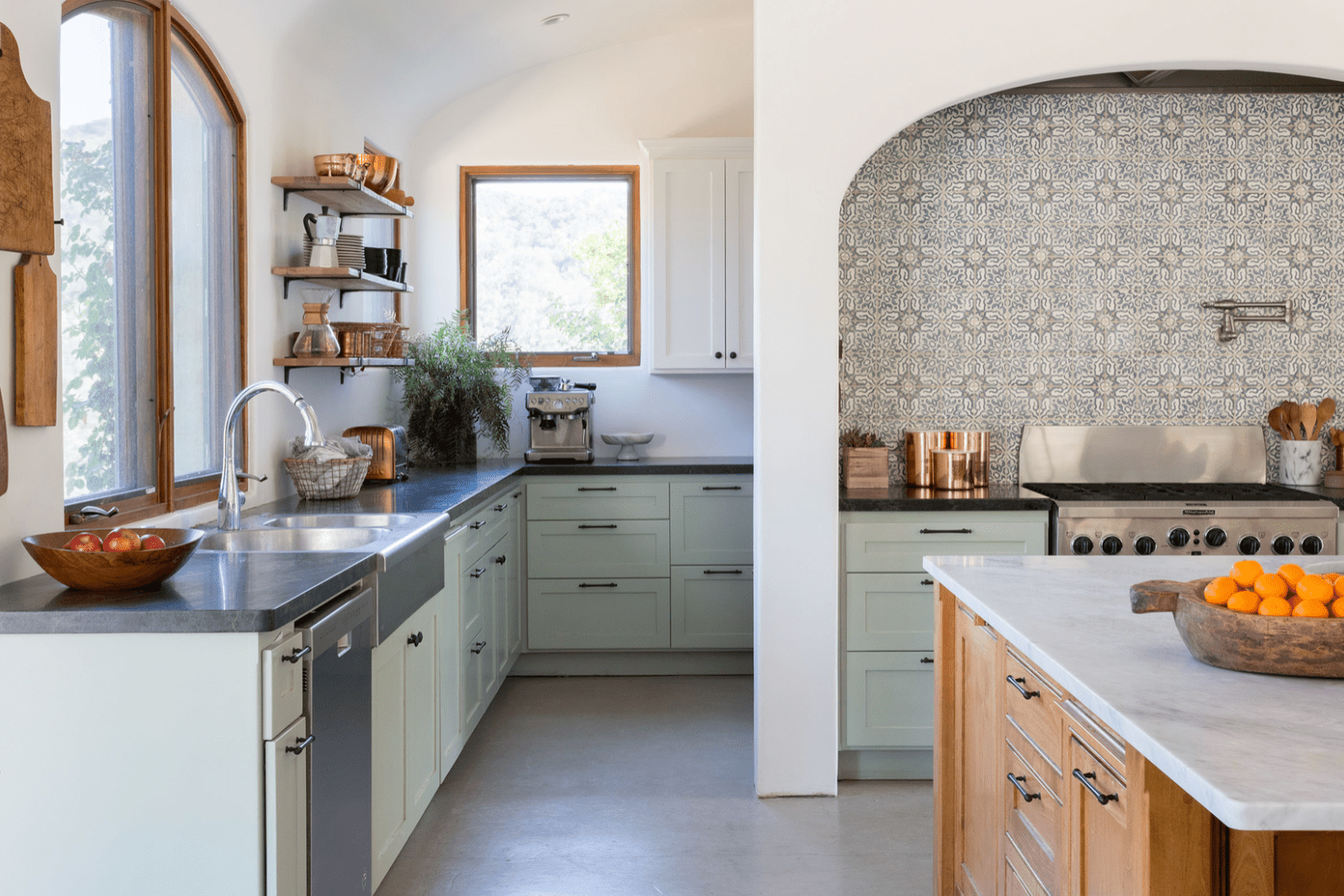 A kitchen with mint green cabinets and a boldly tiled backsplash
