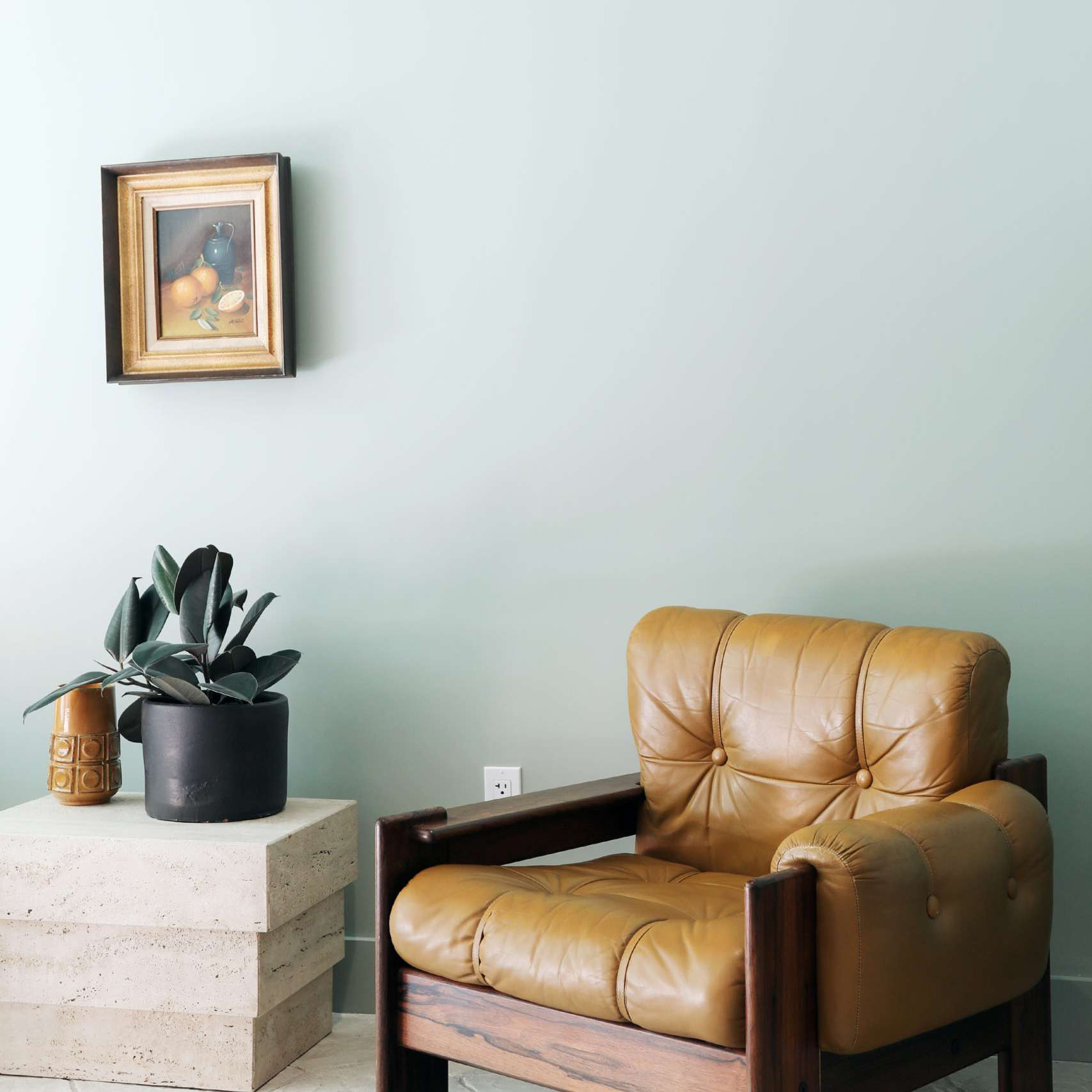 A midcentury modern leather lounger with a concrete side table, potted plant, and ceramic vase.