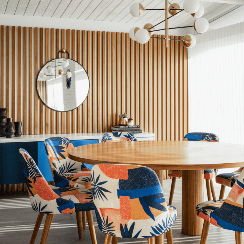 A dining room table surrounded by blue and orange printed upholstered chairs