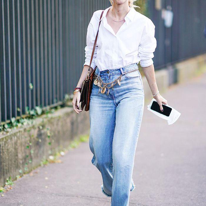 una mujer con botones, cinturón de cadena y jeans acampanados