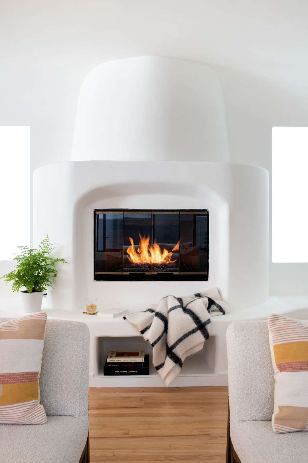 Cozy living room with fireplace, boucle sofas, and knit blanket