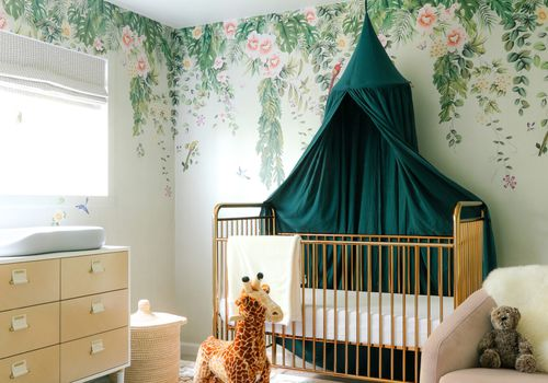 Whimsical nursery with rocking giraffe, floral wallpaper