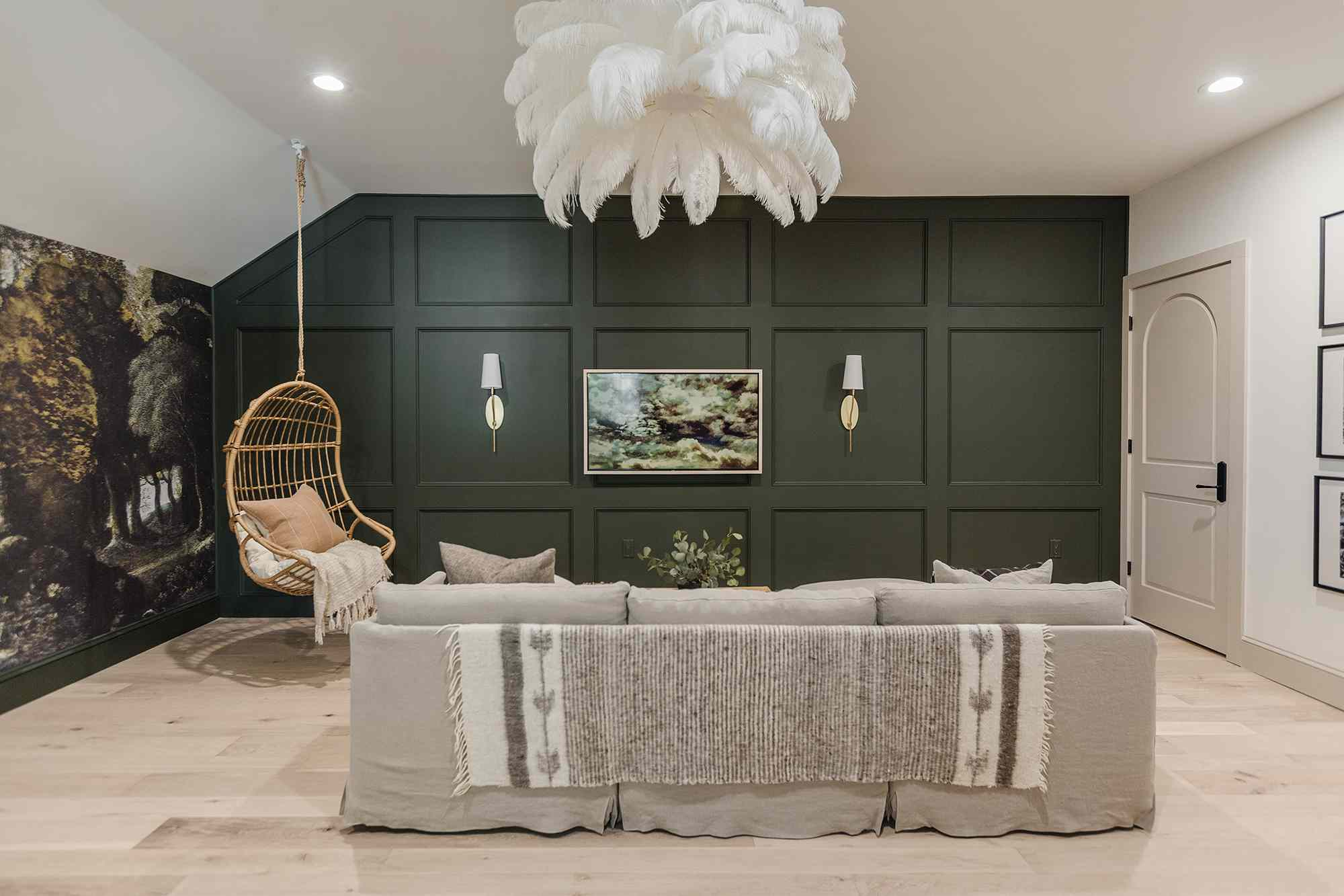 Green coffered wall with hanging rattan chair.