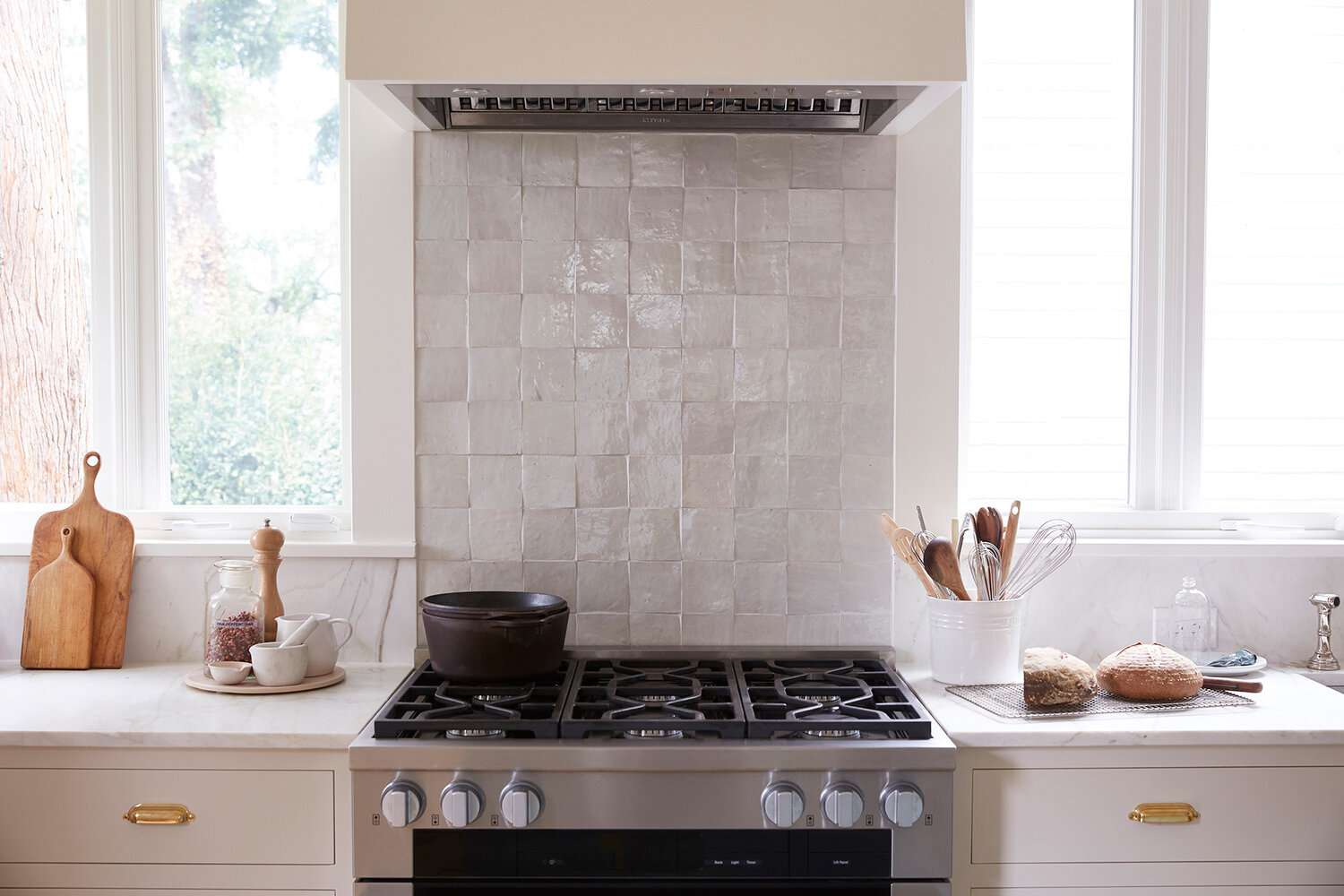 A kitchen backsplash lined with textured white square tiles
