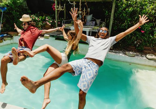 Three young people jump backward into pool fully clothed